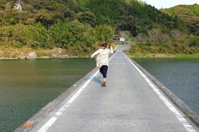 名越屋沈下橋を渡る女性